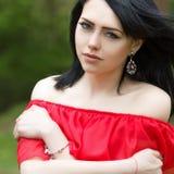 Porträt eines schönen jungen Mädchens mit grünen Augen und bloßen Schultern, in einem roten Kleid auf einer grünen Hintergrundsom lizenzfreies stockfoto