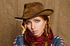 Porträt eines schönen jungen rothaarigen Mädchens in einem Cowboyhut Lizenzfreie Stockbilder