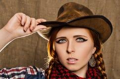 Porträt eines schönen jungen rothaarigen Mädchens in einem Cowboyhut Stockfotografie