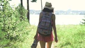 Porträt eines schönen jungen touristischen Mädchens mit einem Rucksack, in einem Strohhut, gehend entlang Felsen, Seehintergrund  stock video