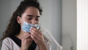 Porträt eines schönen kaukasischen Cosmetologist bereitet sich für den Kunden vor - setzend auf die Maske auf ihrem Gesicht stock video footage