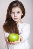 Porträt eines schönen kleinen Mädchens, das einen grünen Apfel hält stockfotografie
