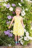Porträt eines schönen kleinen Mädchens im Sommerkleid, Klematisflorida Stockfotografie