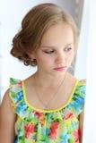 Porträt eines schönen kleinen Mädchens mit dem Haar der Abend im hellen Sommerkleid mit Make-up Lizenzfreies Stockfoto