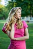 Porträt eines schönen lächelnden jungen netten Mädchens in einem rosa Sommerkleid Lizenzfreie Stockbilder