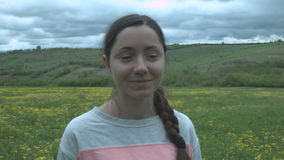 Porträt eines schönen lächelnden Mädchens auf einem Gebiet und dichten Wolken Glückliche junge Frau auf einem Gebiet mit gelben B stock footage
