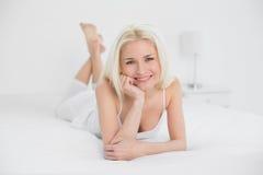 Porträt eines schönen Lächelns blond im Bett Lizenzfreie Stockbilder