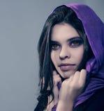 Porträt eines schönen Mädchengesichtes in einem lila Schalgesicht Lizenzfreie Stockfotografie