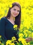 Porträt eines schönen Mädchens auf dem Rapsgebiet Stockbild