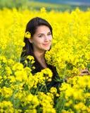 Porträt eines schönen Mädchens auf dem Rapsgebiet im Sommer Lizenzfreie Stockfotos