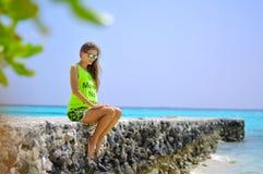 Porträt eines schönen Mädchens, das auf dem Pier am tropischen Strand sitzt Lizenzfreie Stockfotografie
