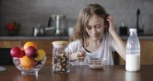 Porträt eines schönen Mädchens, das Getreide mit Milch isst stock video footage
