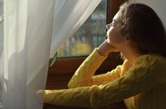 Porträt eines schönen Mädchens, das heraus das Fenster schaut lizenzfreie stockfotos