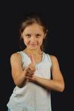 Porträt eines schönen Mädchens, das sich Daumen zeigt Lizenzfreie Stockbilder