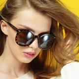 Porträt eines schönen Mädchens in den Gläsern auf einem gelben Hintergrund im Studio Lizenzfreie Stockbilder
