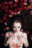 Porträt eines schönen Mädchens in den rosafarbenen Blumenblättern Lizenzfreie Stockfotos