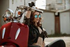 Porträt eines schönen Mädchens in der Lederjacke, Büstenhalter und Gläser nähern sich rotem Motorrad stockfotos