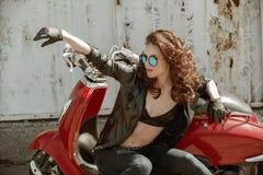Porträt eines schönen Mädchens in der Lederjacke, Büstenhalter und Gläser nähern sich rotem Motorrad stockfotografie