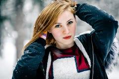 Porträt eines schönen Mädchens in der schwarzen Jacke mit Pelzhaube unter Winterwald stockfotografie