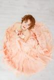 Porträt eines schönen Mädchens in einem beige Pfirsichkleid Stockfotos
