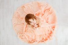 Porträt eines schönen Mädchens in einem beige Pfirsichkleid Lizenzfreie Stockfotografie