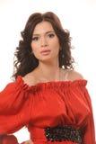 Porträt eines schönen Mädchens in einem roten Kleid auf einem weißen Hintergrund. Lizenzfreies Stockbild