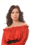 Porträt eines schönen Mädchens in einem roten Kleid auf einem weißen Hintergrund. Lizenzfreie Stockfotografie