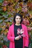 Porträt eines schönen Mädchens in einem roten Mantel stockfoto