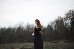 Porträt eines schönen Mädchens in einem schwarzen Mantel auf der Natur Stockfoto
