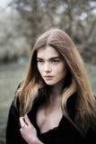 Porträt eines schönen Mädchens in einem schwarzen Mantel auf der Natur stockbild