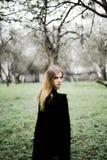 Porträt eines schönen Mädchens in einem schwarzen Mantel auf der Natur lizenzfreies stockfoto