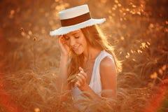 Porträt eines schönen Mädchens in einem weißen Kleid und in einem Hut im fie Lizenzfreies Stockbild