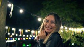 Porträt eines schönen Mädchens in einer schwarzen Lederjacke, die im Nachtpark steht Licht von bunten Lampen eines Cafés an stock video footage