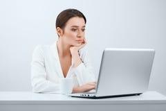 Porträt eines schönen Mädchens im Büro, das an dem Computer arbeitet Stockfotos