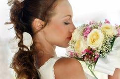 Porträt eines schönen Mädchens im Weiß mit einem Hochzeitsblumenstrauß. Lizenzfreie Stockfotografie