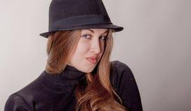 Porträt eines schönen Mädchens mit dem langen Haar in einem Hut Stockfotos