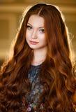 Porträt eines schönen Mädchens mit dem langen roten Haar in einem grünen Kleid Stockfotografie