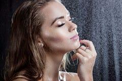 Porträt eines schönen Mädchens mit dem nassen Haar unter Wassertropfen Lizenzfreies Stockbild