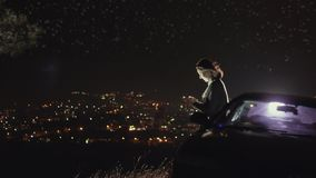 Porträt eines schönen Mädchens mit einem Smartphone auf dem Hintergrund der Nachtstadt und des sternenklaren Himmels stock video footage