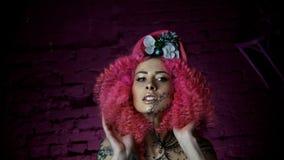 Porträt eines schönen Mädchens mit stilvollem Haarschnitt des gelockten Rosahaares L stock footage
