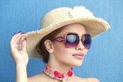 Porträt eines schönen Modemädchens in einem Hut auf einem blauen Hintergrund Stockbild