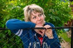 Porträt eines schönen russischen Mädchens in einem Park am Zaun Stockbilder