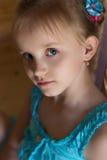 Porträt eines schönen süßen kleinen Mädchens in einem blauen Kleid mit blauen Augen Lizenzfreies Stockfoto