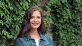 Porträt eines schönen stilvollen Mädchens, das kokett an der Kamera lächelt stock footage