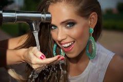 Porträt eines schönen Trinkwassers der jungen Frau Lizenzfreie Stockfotografie