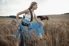 Porträt eines schönen weiblichen Cowgirls mit Schrotflinte vom wilden Westreiten ein Pferd im Hinterland Stockbild