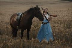 Porträt eines schönen weiblichen Cowgirls mit Schrotflinte vom wilden Westreiten ein Pferd im Hinterland Lizenzfreies Stockfoto