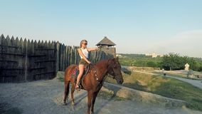 Porträt eines schönen weiblichen Cowgirls mit Schrotflinte vom wilden Westreiten ein Pferd im Hinterland stock footage