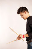 Porträt eines Schlagzeugers, der mit tragendem Schwarzem des Trommelstockes im Studio spielt Lizenzfreies Stockfoto
