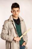 Porträt eines Schlagzeugers mit dem Trommelstock, der einen Mantel trägt und greeen Hemd im Studio Lizenzfreies Stockfoto